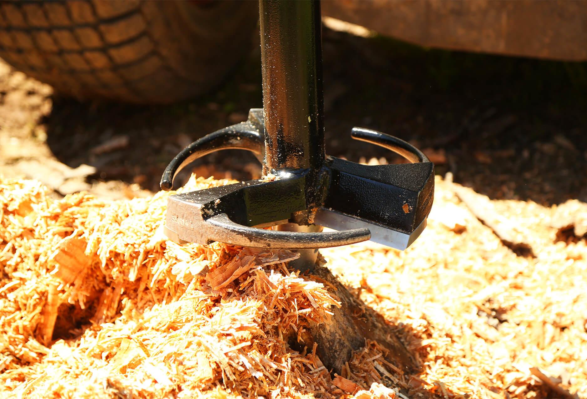 skid steer auger stump planer removing a tree stump.