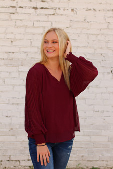 mariah long sleeve blouse  - a burgundy color blouse with sheer bell sleeves  - model is wearing a size small