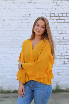 scarlet ruffled top  - a mustard color dressier top, with ruffles on the sleeves  - model is wearing a small