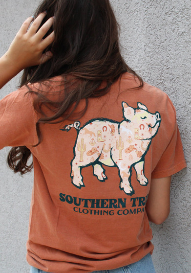 a burnt orange comfort colors tee with a western pig on the back