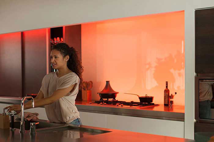 Couple sat on sofa watching television lit by Philips Hue products