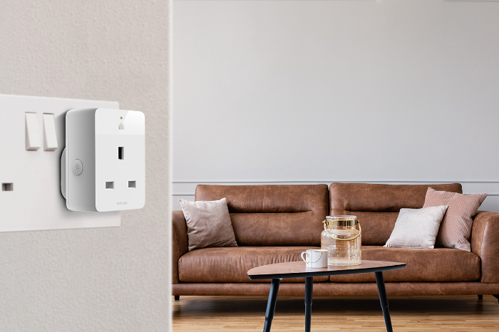 Tp-link smart plug on the wall of a living room showing a sofa