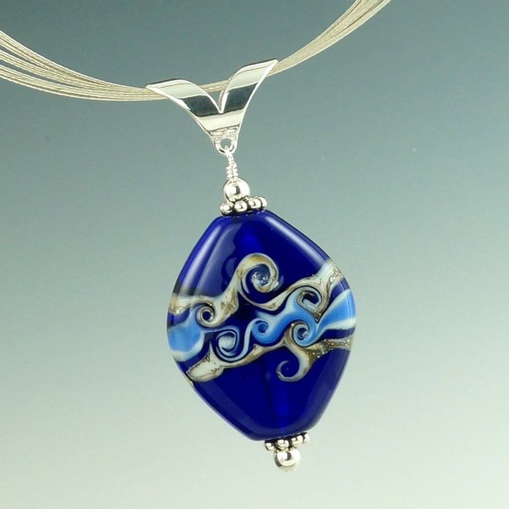 A beautiful base of deep cobalt blue with rich layers of ivory and blue glass with silver make this swirl pendant really pop. After shaping, the surface of one side is heated and then swirled with a thin rod of glass to create its own beautiful design, while the other side is left natural. Each each side offers its own distinct style.