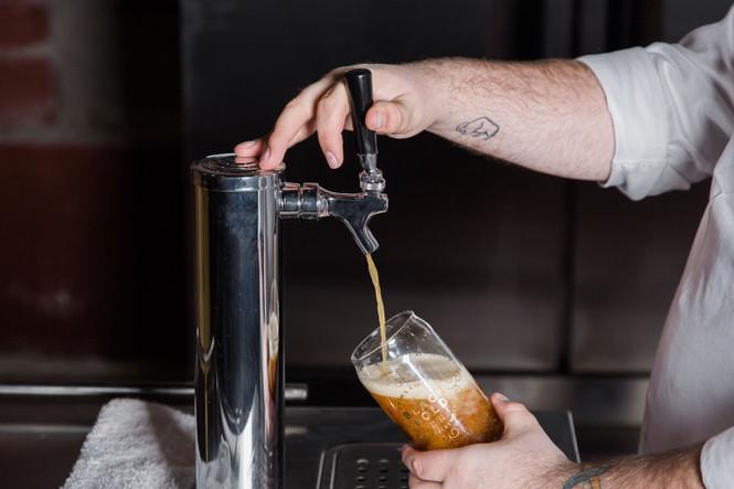 Bartender filling beer glass