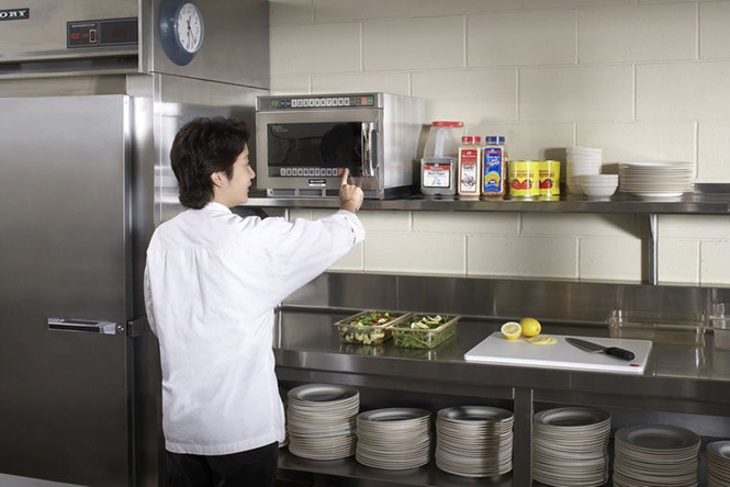 A chef reaches toward the bottom control panel on a Sharp TwinTouch microwave