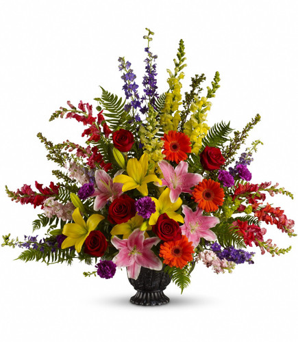Walk Among the Rainbows Funeral Bouquet from Sympathy Flower Shop. The tastefully colorful bouquet includes red roses, light pink oriental lilies, yellow asiatic lilies, orange gerberas, purple carnations, orange snapdragons, yellow snapdragons, lavender larkspur, pink stock and bupleurum accented with greenery. SKU SYM444