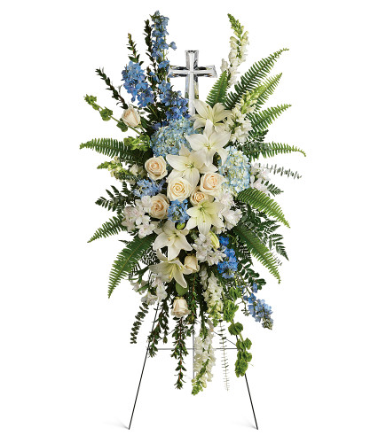 Crystal Cross Standing Spray from Sympathy Flower Shop. This serene spray includes blue hydrangea, white roses, white oriental lilies, white alstroemeria, bells of Ireland, blue delphinium, white snapdragons, myrtle, sword fern, spiral eucalyptus, and assorted greenery. Delivered on a wire funeral easel with a Large Crystal Cross Keepsake. SKU SYM618