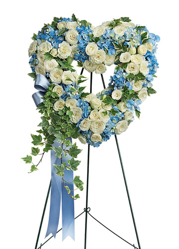 "Pure Love White Rose and Blue Hydrangea Heart Shaped Spray from Sympathy Flower Shop. This heartfelt spray of flowers features blue hydrangeas, white mini spray roses, and variegated ivy. Delivered on a wire easel. Approximately 21"" W x 30"" H SKU SYM103"