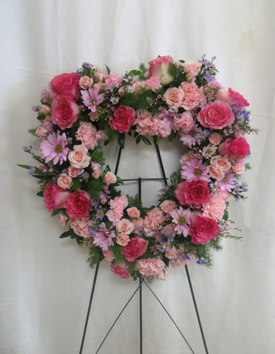 "Always Loved Pink Rose Funeral Heart Wreath from Sympathy Flower Shop. This heart shaped standing spray arrives on a metal funeral easel and includes hot pink roses, hot pink mini spray roses, lavender daisies, light pink mini pixie carnations, pink carnations and lavender filler flowers. Heart is approximately 22"" W x 22"" H SKU SYM111"