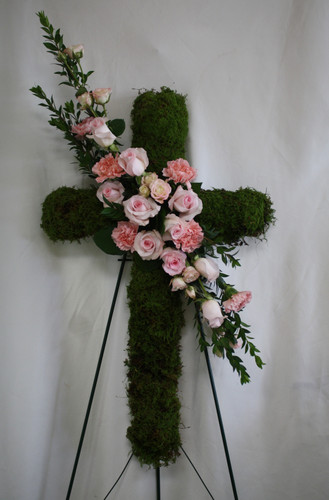 "Pink Rose Funeral Flower Cross from Sympathy Flower Shop. The moss-covered cross features a diagonal swag of pink roses and pink carnations, and is delivered on an easel. Approximately 20"" W x 32"" H  SKU SYM306"