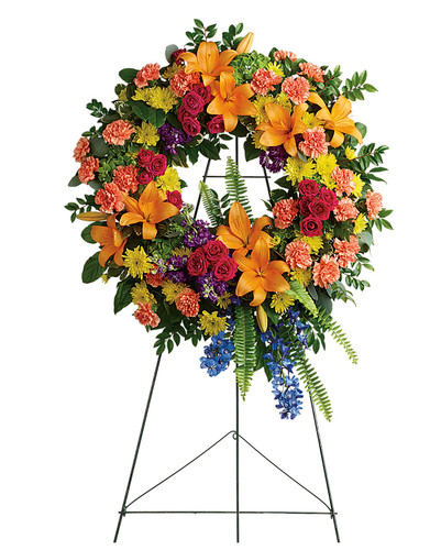 "Bright and Colorful Orange Lily Funeral Wreath from Symapthy Flower Shop. Our funeral wreath features green hydrangea, hot pink spray roses, orange asiatic lilies, orange carnations, blue delphinium, purple stock, yellow cushions, sword fern, silver dollar eucalyptus, and various greenery. Delivered on a sympathy wire easel. Approximately 24"" W x 34"" H   SKU SYM202"