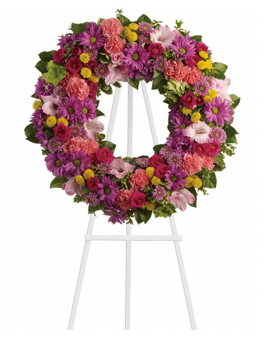 "Ringed In Love Pink Funeral Flower Wreath from Sympathy Flower Shop. A standing sympathy wreath of dazzling flowers such as green hydrangeas, hot pink spray roses, pink gladioli and carnations along with a mélange of multi-colored daisies and cushions and greenery is delivered on an easel. Approximately 22"" W x 22"" H  SKU SYM203"