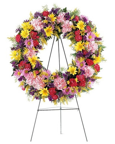 "For Eternity Wreath Shaped Funeral Spray of Pink Flowers from Sympathy Flower Shop. Your wreath is decorated with pink carnations, lavender and yellow daisies, plus colorful fillers and soft foliages. The wreath is delivered on an easel. Approximately 22""H x 22""W  SKU SYM210"