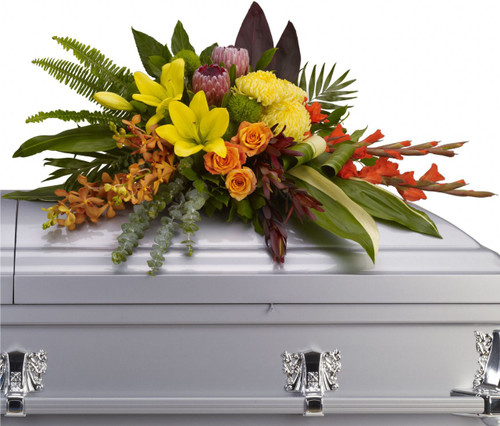 Tropical Memorial Orchid & Protea Casket Cover Spray from Sympathy Flower Shop. This funeral casket spray includes yellow asiatic lilies with orange orchids and roses, red gladiolias, pink protea and yellow mums draped across the casket amidst radiating ferns, greens and leaves.  SKU SYM821