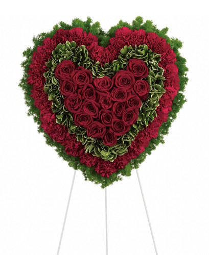 "Eternal Love Red Heart Sympathy Spray from Sympathy Flower Shop. This solid red roses matched with deep red carnations are surrounded by variegated greens and fern and is delivered on a wire funeral easel. Approximately 21"" W x 21"" H (size does not include easel) SKU SYM104"