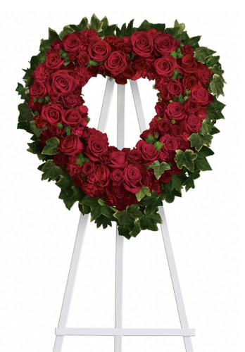 "Blessings Red Rose Open Heart Funeral Spray from Sympathy Flower Shop. Your heart shaped funeral wreath includes big red roses, petite red spray roses, red carnations and red miniature pixie carnations and are arranged with fern and ivy greens and arrives on a wire funeral stand. Approximately 20"" W x 20"" H  SKU SYM102"