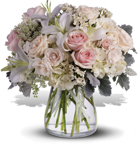 Whispering Love Sympathy Bouquet by Sympathy Flower Shop. Gorgeous flowers such as white, crème and light pink roses, white oriental lilies and filler flowers with a touch of silvery dusty miller, all in a classic clear vase. Your Pearland funeral florist. SKU SYM422