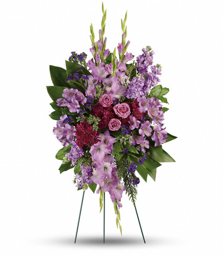 Purple Reflections Standing Spray from Sympathy Flower Shop. This royal and regal spray includes lavender roses, lavender alstroemeria, lavender gladioli, lavender stock, purple cushion spray chrysanthemums, purple sinuata statice, green ti leaves, flat cedar, oregonia and lemon leaf. Delivered on a wire funeral easel. SKU SYM614