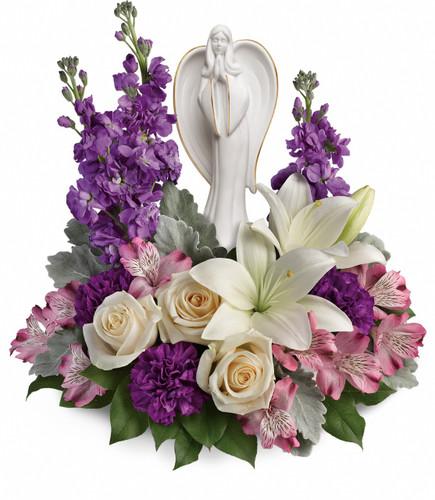"Purple Flowers with Beautiful White Angel Keepsake Bouquet from Sympathy Flower Shop.This royal arrangement includes crème roses, white lilies, lavender alstroemeria, purple carnations, lavender stock, and lemon leaf. Bouquet size is approximately 14"" W x 14"" H SKU SYM449"