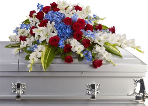 Red White & Blue Patriotic Casket Spray from Sympathy Flower Shop. The bright flowers include blue hydrangeas, white oriental lilies, blue delphinium, red roses, and much more create this dignified way to honor the any deceased loved one. SKU SYM804