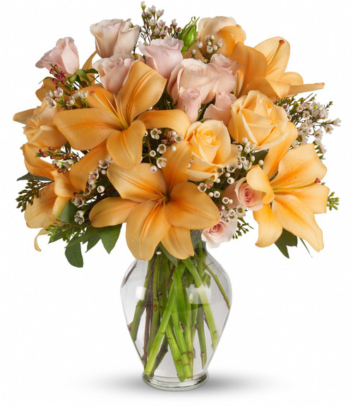 Warm Your Heart Sympathy Bouquet from Sympathy Flower Shop. The sunny bouquet includes crème roses, peach spray roses, orange asiatic lilies and white waxflower accented with fresh greenery. Delivered in a classic glass vase. SKU SYM443