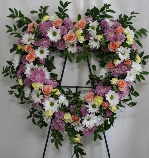 """Loving Lavender & Pink Heart Tribute of Funeral Flowers from Sympathy Flower Shop. This heart shaped funeral spray is created with lavender mums, white daisies, yellow mini pixie carnations, pink mini pixie carnations and light pink spray roses, delivered on a metal funeral easel. Approximately 22"""" W x 22"""" H  SKU SYM110"""