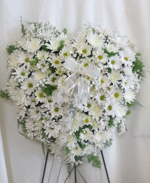 "Purest Soul All White Heart Shaped Funeral Wreath from Sympathy Flower Shop. Our standing spray heart will arrive on a metal funeral easel and includes white daisies, white mums, and white baby's breath throughout the entire heart. Solid white heart is approximately 20"" W x 22"" H SKU SYM112"