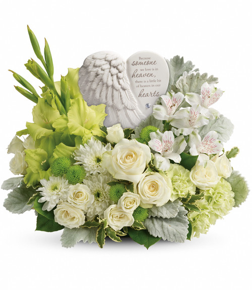 "Hearts in Heaven Keepsake with Green Funeral Flowers from Sympathy Flower Shop. This funeral bouquet includes white spray roses, white alstroemeria, green gladioli, green carnations, green button spray chrysanthemums, and white cushion spray chrysanthemums and is accented with pitta negra and lemon leaf.  Your sympathy flowers include the Heaven's Heart Keepsake, approximately 6""H x 6""W. Heart scripture read, ""Because someone we love is in heaven, there is a little bit of heaven in our hearts."" Funeral flowers are approximately 16"" W x 13"" H. SKU SYM464"