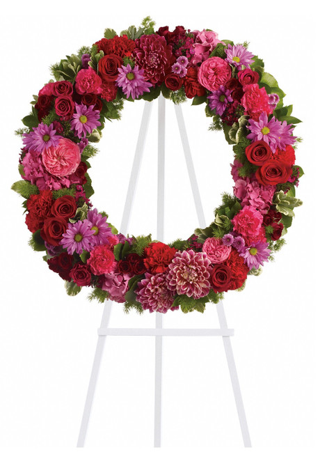 "Infinite Love Large Hot Pink Funeral Flower Wreath from Sympathy Flower Shop. The design includes dazzling blooms such as pink hydrangeas, hot pink roses and carnations, red roses, spray roses and carnations, lavender daisies and buttons, with fern and other fresh greens to create a beautiful wreath that comes delivered on a sympathy easel. Approximately 27"" W x 27"" H  SKU SYM204"
