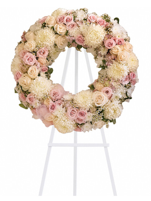 """Eternal Peace White and Pink Funeral Wreath Spray from Sympathy Flower Shop. Gorgeous pink hydrangeas, crème roses, light pink spray roses, white chrysanthemums, waxflower and more are adorned by pink ribbons in this eternal circle of peace. Approximately 22"""" W x 22"""" H (Size does not include easel) SKU SYM206"""