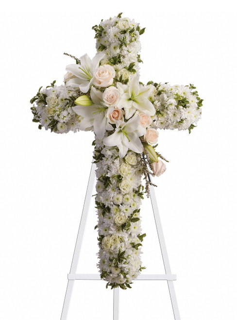 """White Lily Funeral Cross of Flowers from Sympathy Flower Shop. This cross of flowers includes crème roses, white spray roses, oriental lilies, stock, leptosporum, cushion and mums and is a beautiful way to honor a loved one. Approximately 26"""" W x 36"""" H SKU SYM302"""