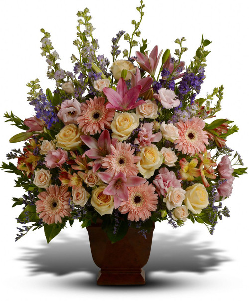 Her Loving Grace by Sympathy Flower Shop. This beautiful bouquet of blossoms includes pink, peach, and lavender flowers of roses, gerbera daisies, lilies, spray roses, alstromeria, lisianthus and larkspur in a traditional funeral urn. From our Houston funeral florist. SKU SYM408