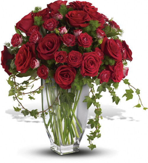 Red Rose Remembrance Bouquet by Sympathy Flower Shop.  Over one dozen brilliant red roses and spray roses along with vibrant fern and ivy are perfectly arranged in an exclusive clear vase. Top Houston funeral florist. SKU SYM417