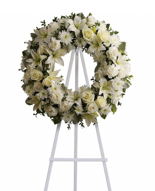 """White Rose Serenity Funeral Wreath Spray from Sympathy Flower Shop. A standing funeral wreath created from fresh white flowers such as roses, Asiatic lilies, carnations and cushions - accented with greenery - is delivered on an easel. Approximately 22"""" W x 22"""" H (Size does not include easel) SKU SYM201"""