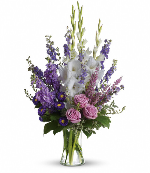 Purple Memories Funeral Arrangement by Sympathy Flower Shop. Lavender and white sympathy flowers make a grand statement in this joyful bouquet. Cherish your memories with this lasting remembrance of lavender larkspur and roses, deep purple asters, pure white gladioli and the softest pink heather. SKU SYM425