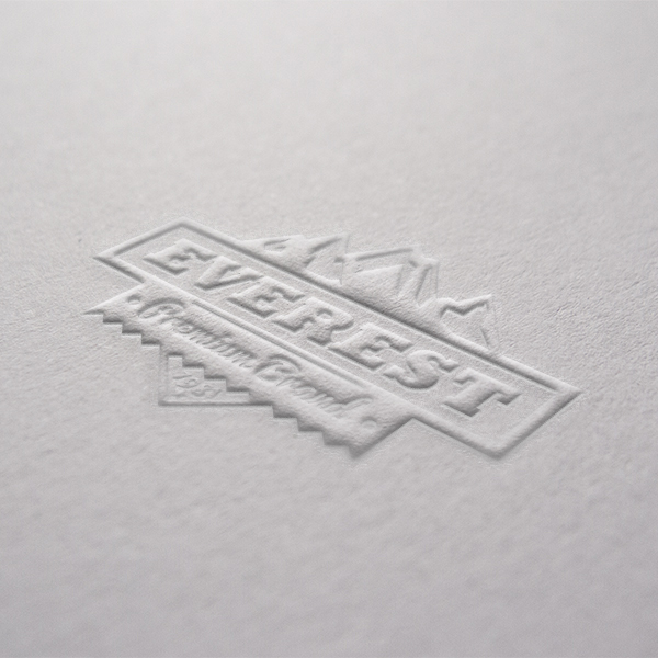 A close up of an embossed everest logo on white paper