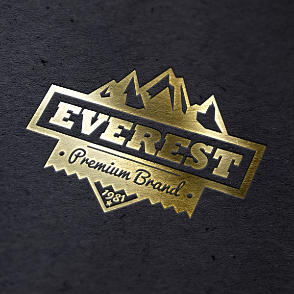 a close up of a gold foiled everest logo on black paper