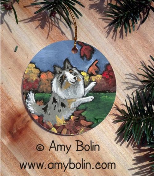 """Chasing Leaves"" Blue Merle Shetland Sheepdog Ceramic Ornament Round"
