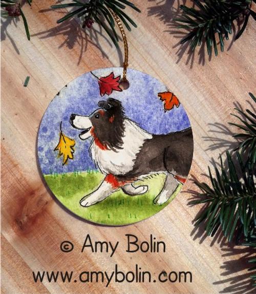 """Chasing Leaves"" Tri Color Shetland Sheepdog Ceramic Ornament Round"