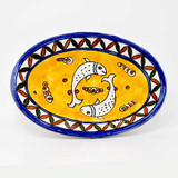 Small ceramic oval dish with fish on a yellow background