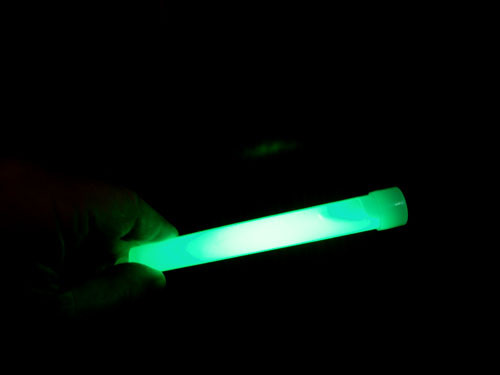 A person holding a green glow Stick.