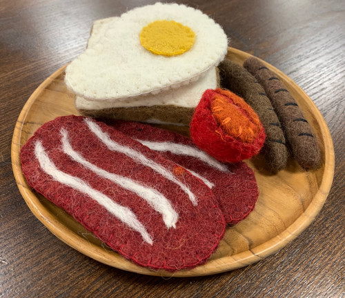 Bacon, eggs, sausages, tomato on a slice of bread, breakfast is served.