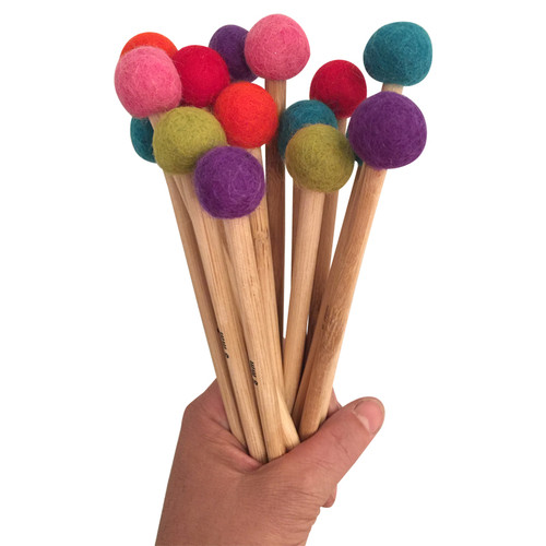 Eight pairs of hand made bamboo knitting needles with different coloured pompoms on top
