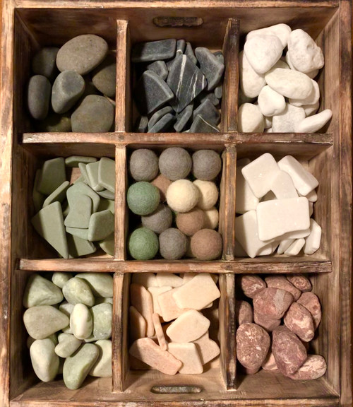 Naturally coloured rocks and similarly coloured felt balls.