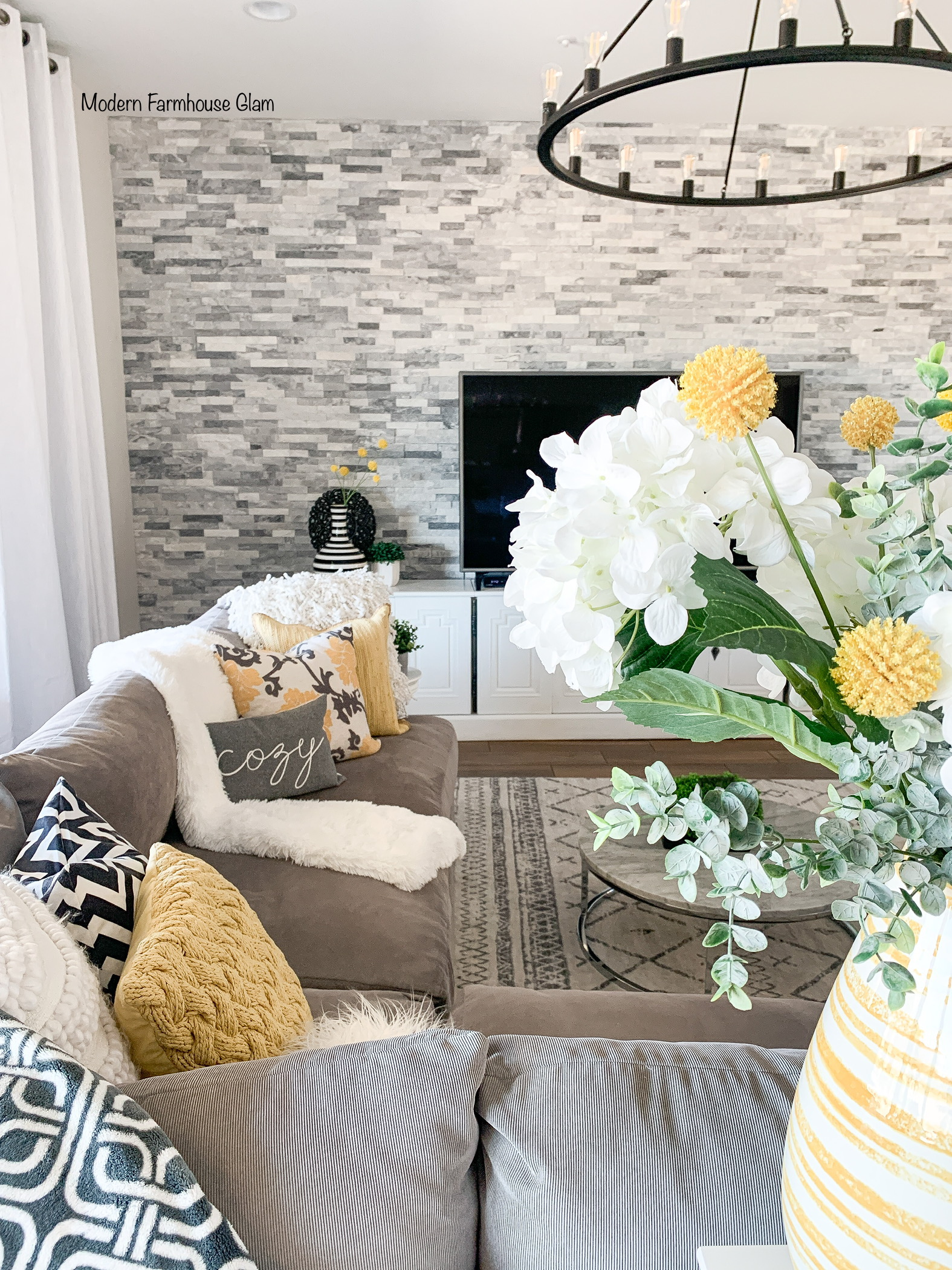 Modern Farmhouse Glam living room furniture, area rug, yellow and grey decorations, lighting, coffee table, accent table, kitchen bar stool