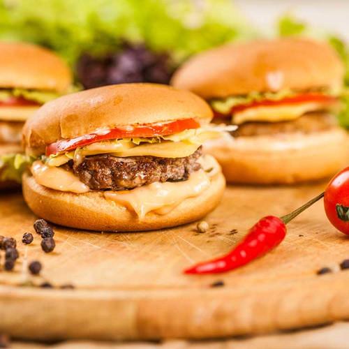 burger sliders all dressed on a wood board
