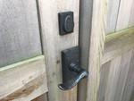 Bronze lever latch and deadbolt on cedar gate