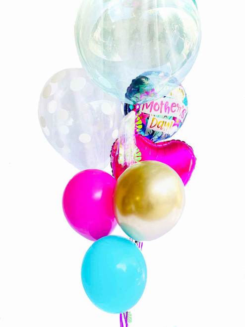 """This tropical Mother's Day bouquet is bright, fun, and unique - just like the special mom in your life. Celebrate her by bringing this beautiful bouquet home loaded with the following balloons:  1 - 18"""" Tropical """"Happy Mother's Day"""" balloon 1- Crystal Clear green tinted 20"""" balloon with handmade iridescent tassel & palm leaf garland. 1- 18"""" Hot Pink foil heart 1- 18"""" Clear Polka Dot Latex Balloon 3 - 11"""" Latex colored balloons ( pink, chrome gold, turquoise)"""