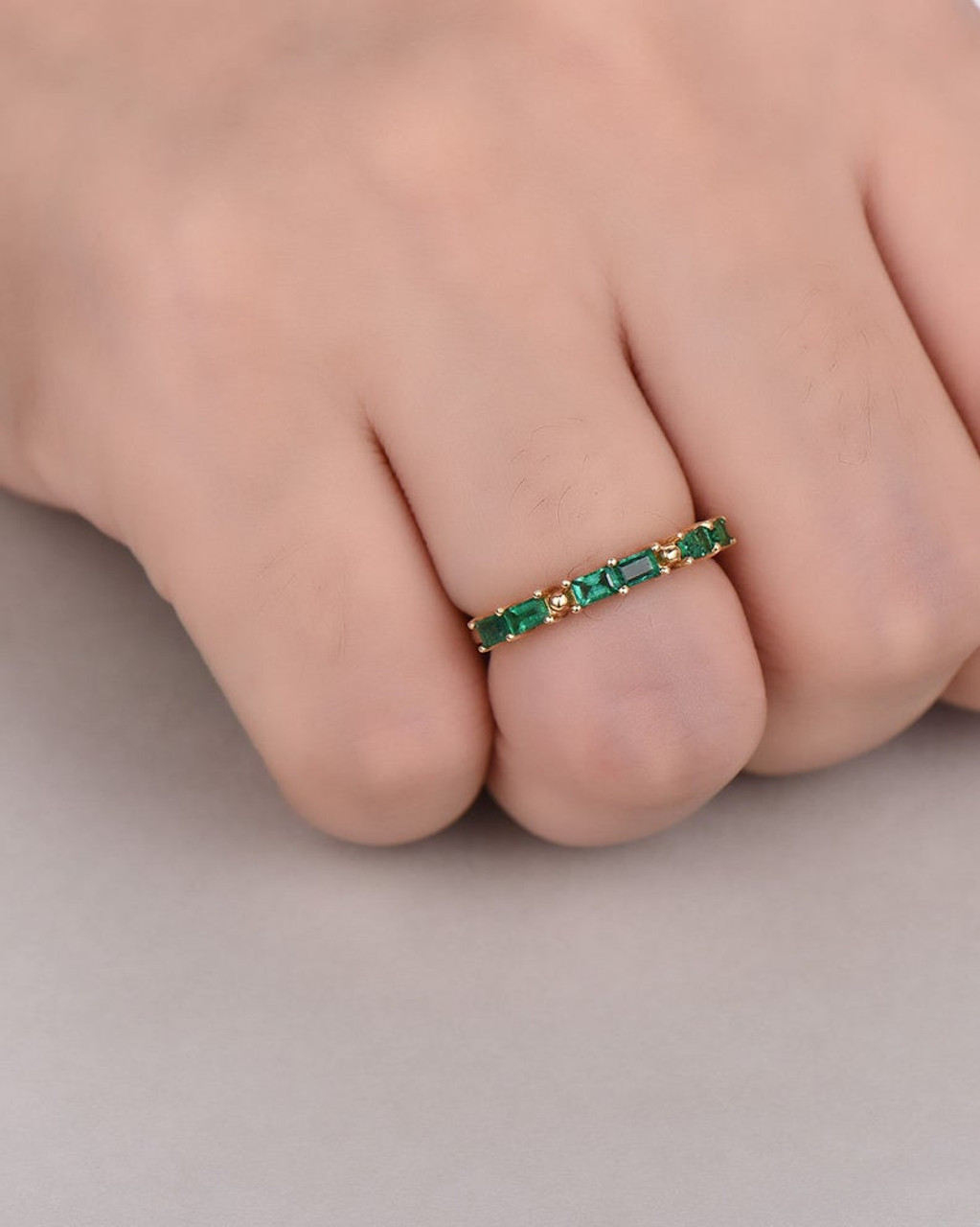 It is a photo of Lab Created Emerald Wedding Band 45k Yellow Gold May Birthstone Bridal Stacking Anniversary Ring