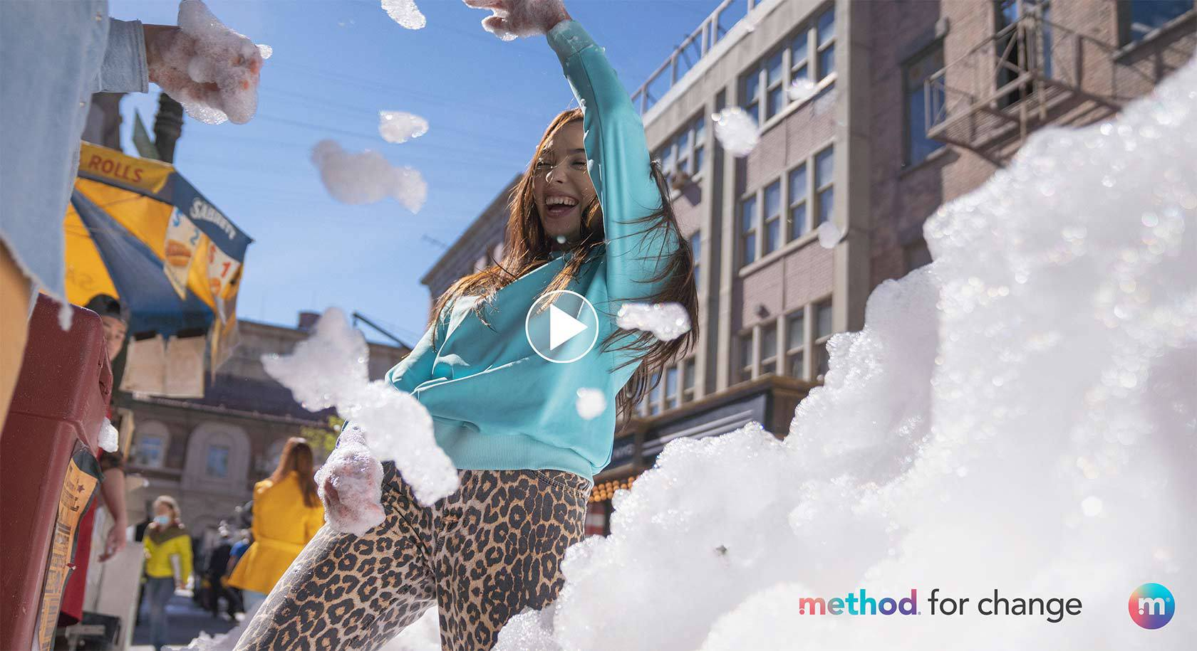 Girl in turquoise sweater standing in the street full of bubbles